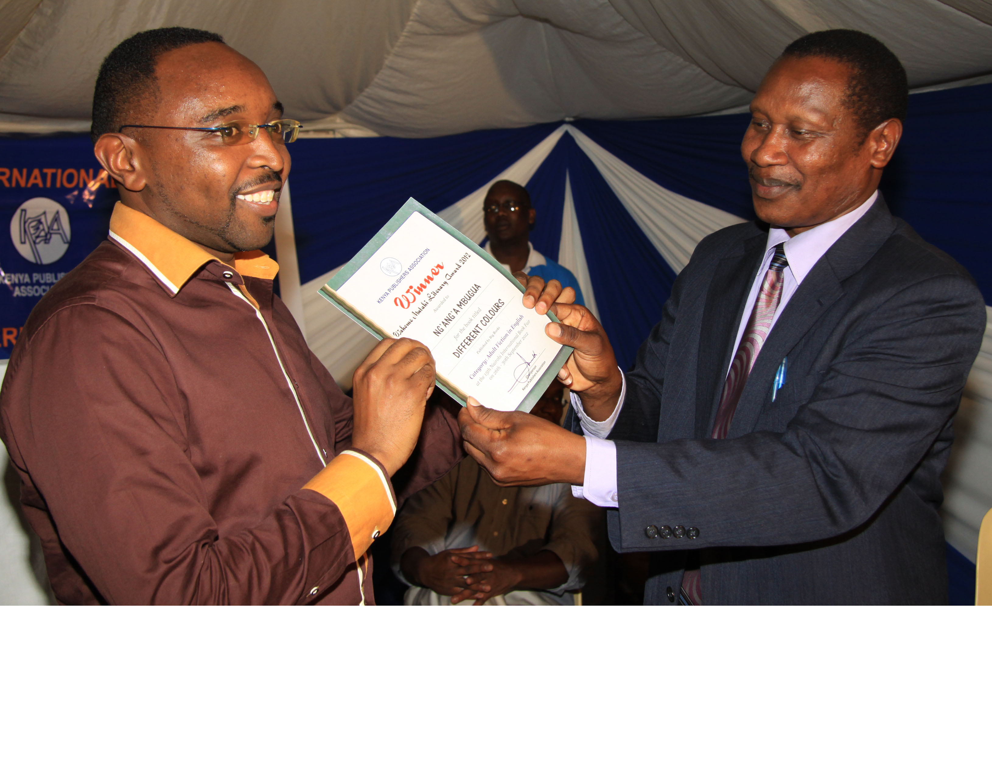 Ng'ang'a Mbugua (Left), is all smiles as he receives his winner's certificate from Prof Egara Kabaji, who was the chief guest at the ceremony